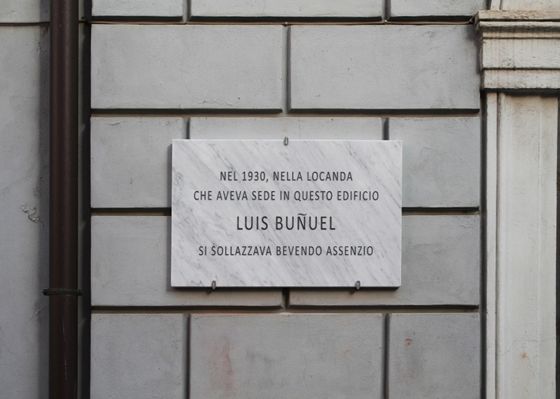 Francesco Fossati, Fake History [BUNUEL], 2015, installation view, historic center of Carrara IT, Carrara Marble plaque, 80 x 50 x 3 cm IN 1930, IN THE INN LOCATED IN THIS BUILDING LUIS BUNUEL USED TO GET AMUSED DRINKING ABSINTHE Nel 1930, nella locanda che aveva sede in questo edificio Luis Bunuel si sollazzava bevendo assenzio