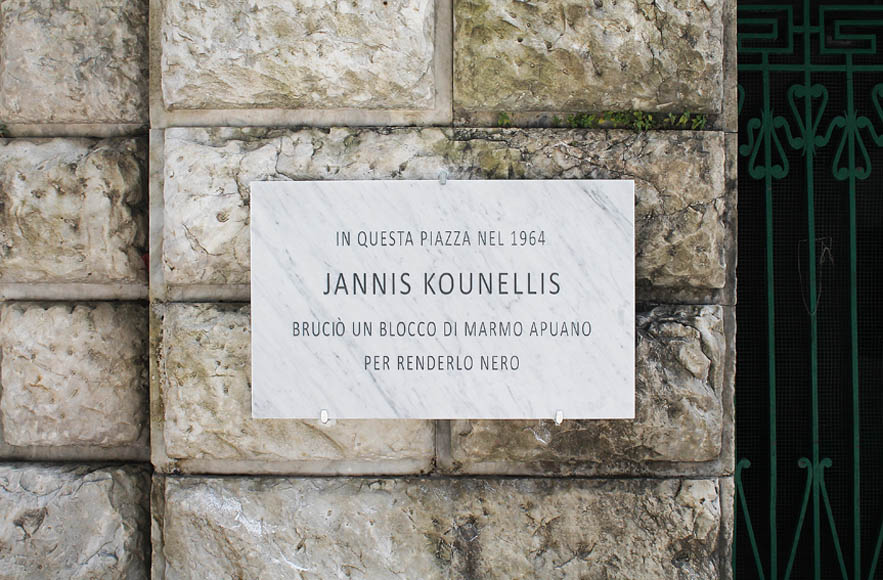 Francesco Fossati, Fake History [KOUNELLIS], 2015, installation view, historic center of Carrara IT, Carrara Marble plaque, 80 x 50 x 3 cm IN THIS SQUARE, IN 1964, JANNIS KOUNELLIS HAS BURNED A LOCAL MARBLE PIECE TO MAKE IT BLACK In questa piazza nel 1964 Jannis Kounellis bruciò un blocco di marmo apuano per renderlo nero